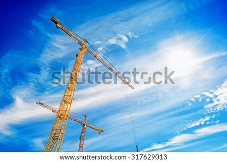 Two Yellow Industrial Cranes Working on Construction Site Against Blue Sky - stock photo