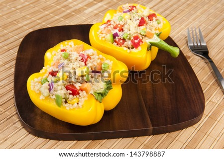 Two yellow peppers stuffed with quinoa and mixed vegetables - stock photo