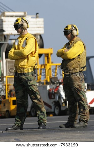 "Two ""Yellow Shirt"" Aircraft Directors Stand on the Flight Deck of a Nuclear Aircraft Carrier - stock photo"