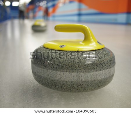 Two yellow stones for game in curling on ice. - stock photo