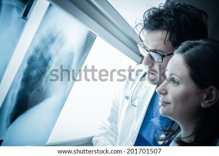 two yound doctors examining a x-ray film at the diaphanoscope - stock photo