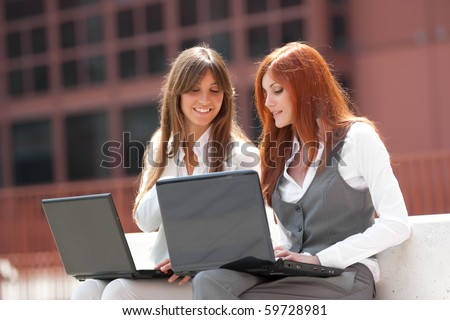 two young adult caucasian businesswoman,working outdoors with two laptop - stock photo