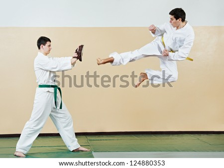 Two young adult people in kimono training taekwondo martial art at gym - stock photo