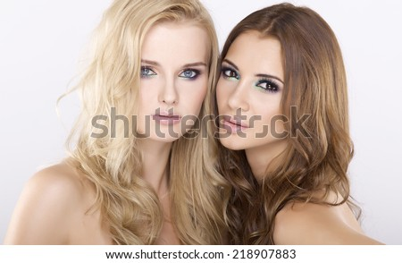 Two young adult sensuality attractive girl friends - blond and brunette pretty woman on white background - stock photo