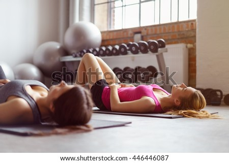 Two young adult women resting their core muscles on individual rectangular mats with weights and stability ball in background in fitness room - stock photo