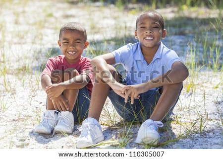 Two young African American boy children sitting together in the summer sunshine - stock photo