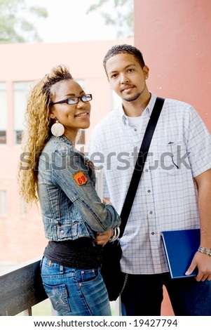 Two young african college students standing and chatting in the passage before going to the classroom - stock photo