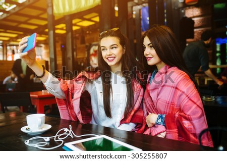 Two young and beautiful girl sitting at the table and doing selfie in the cafe - stock photo
