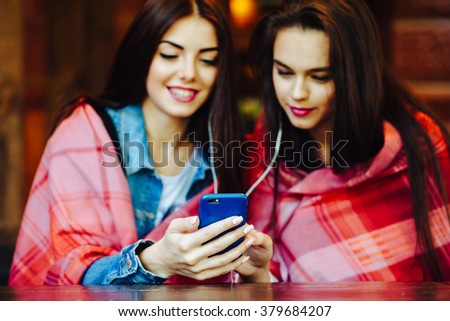 Two young and beautiful girl sitting at the table listening to music with a smartphone - stock photo