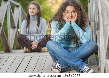Two young and beautiful girls at banisters of little bridge in city-park. - stock photo