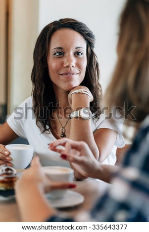 Two young and beautiful women meet at the bar for a cappuccino and to chat. A woman speaks gesturing while the other is listening smiling - stock photo