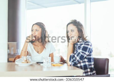 Two young and beautiful women meet at the bar for a cappuccino and to chat .Both observe the inside of the bar - stock photo