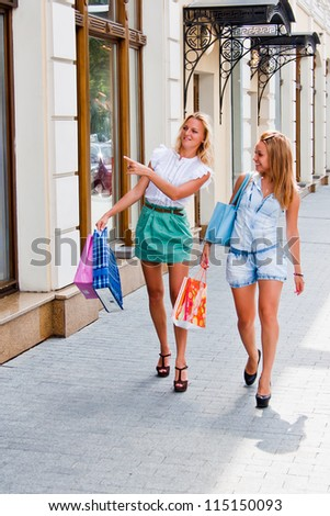 Two young and beautiful women walking down the street with shops - stock photo