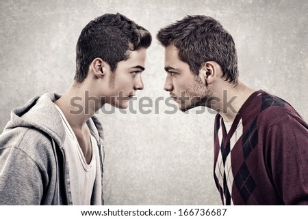 Two young angry people standing face to face - stock photo