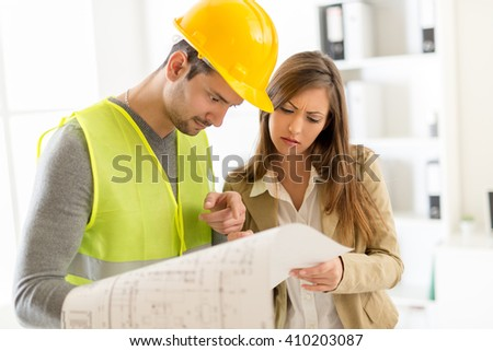 Two young architects discussing construction plans in office. - stock photo