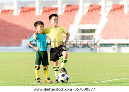 Two Young Asian boy stand in the grass football field in the stadium during summer. - stock photo