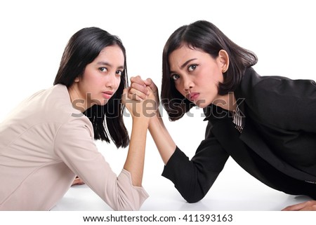 Two young Asian businesswomen with arms wrestled looking at camera aggressively, isolated on white background - stock photo