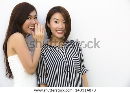 Two young Asian good friends sharing secrets. - stock photo