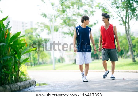 Two young athletic friends walking in the park and talking - stock photo