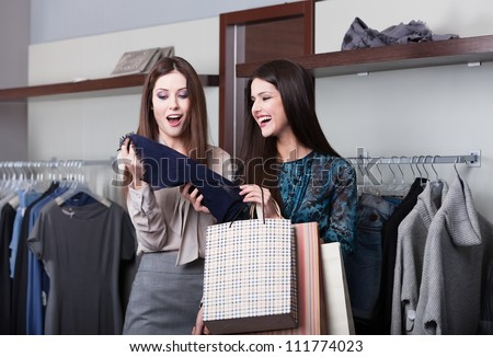 Two young attractive girlfriends go shopping - stock photo