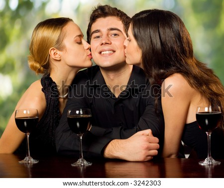 Two young attractive sweet women kissing man with redwine glasses at the celebration or party - stock photo