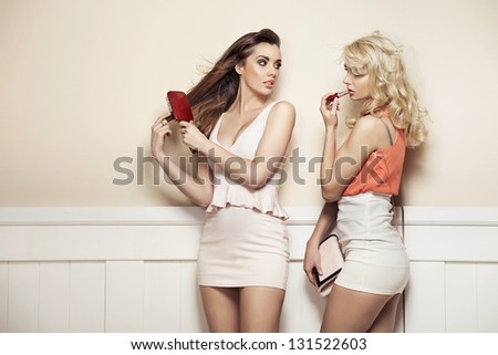 Two young beauties making preparations to a party - stock photo