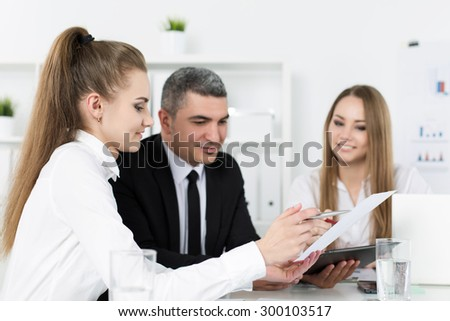 Two young beautiful business women consulting with their colleague. Partners discussing documents and ideas - stock photo