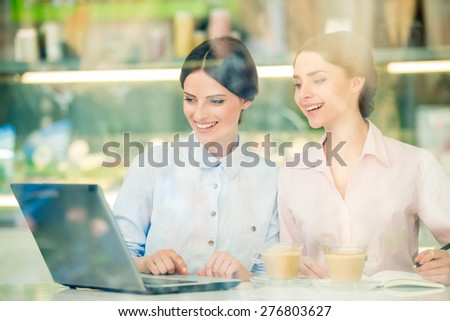 Two young beautiful businesswomen  sitting in urban cafe and using laptop. - stock photo