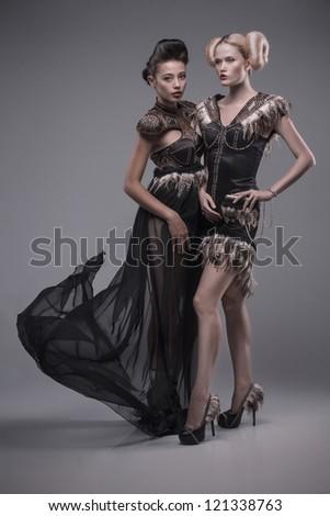 two young beautiful caucasian women in gorgeous dress, motion shot - stock photo