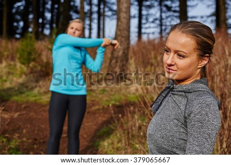 two young beautiful girls after run playing with hair, girl stretching in back - stock photo