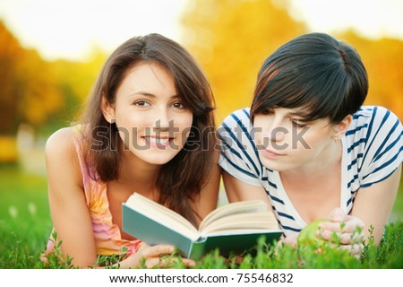 Two young beautiful girls lying on the lawn and read a book - stock photo