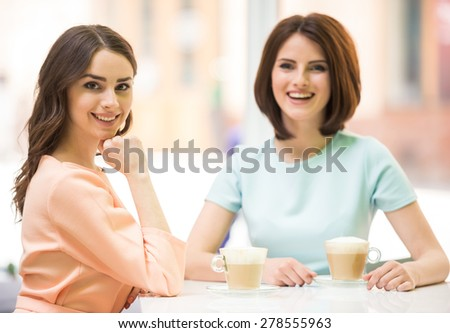 Two young beautiful girls sitting in urban cafe  and drinking coffee with cream. - stock photo