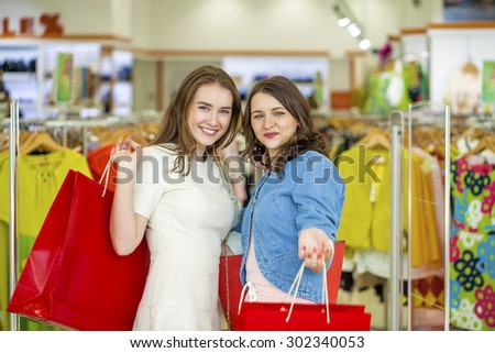 Two young beautiful girls standing at the storefront with shopping bags - stock photo