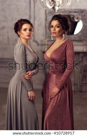 Two young beautiful ladies posing in fashionable evening dresses in luxury interior - stock photo