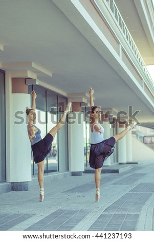 Two young beautiful twin sister dancing ballet in the city with ballet costume. urban sync dance. industrial street dancing. with special effect. synced posing. pointe ballet shoes and dress. - stock photo
