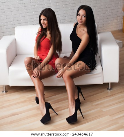 Two young beautiful woman smiling in black and red dress over white background  - stock photo