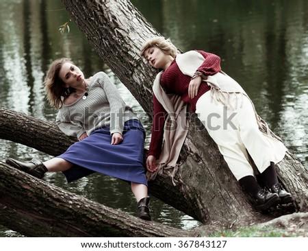 two young beautiful women posing on a tree.  - stock photo