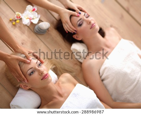 Two young beautiful women relaxing and enjoying at the spa  - stock photo