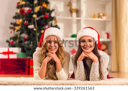 Two young beautiful women while celebrating Christmas at home - stock photo