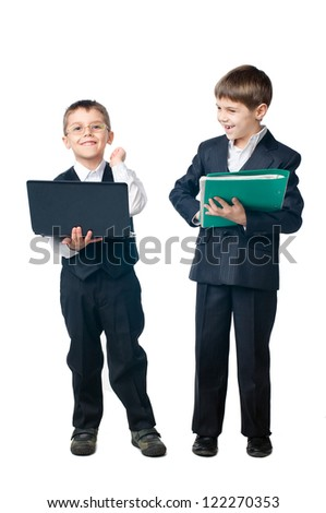 Two young boys dressed up in suits holding laptop and folder, isolated on white background - stock photo
