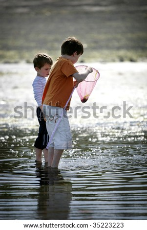 two young boys exploring the ocean with a net - stock photo
