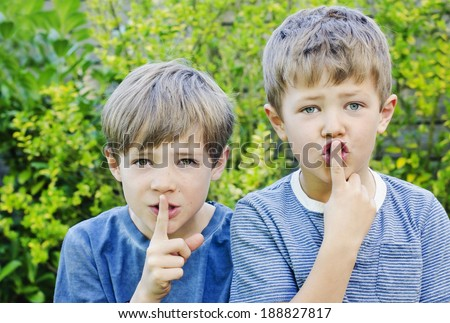Two young boys holding their fingers to their lips  to keep a secret - stock photo