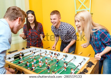 Two young boys laughing and having a duel playing table hockey, while two girls cheering them up making applause and rooting for them in a yellow room  - stock photo