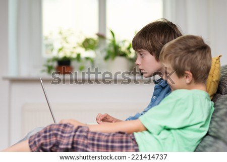 Two young boys, or brothers, sitting on a sofa playing on a laptop computer , side view in front of a window - stock photo