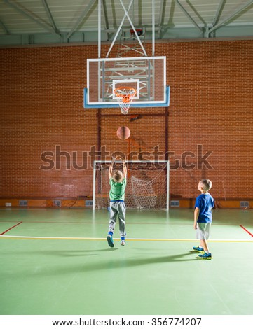 Two young boys playing basketball together on an indoor court shooting for goal as they enjoy their vacation - stock photo