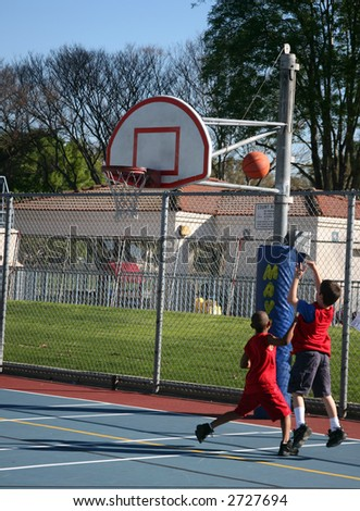 Two young boys shooting some hoops at the park - stock photo