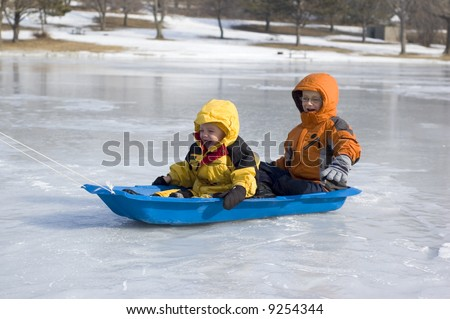 Two Young Boys Sled on Icy Lake - stock photo