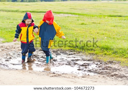 Two young brothers in the puddle, holding hands - stock photo