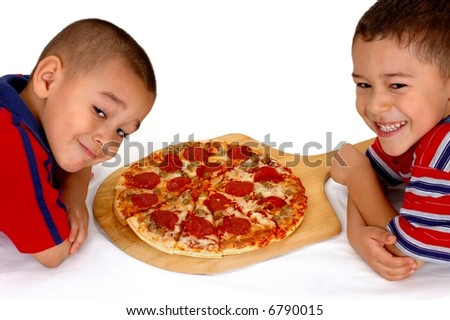 Two young brothers ready to eat a pepperoni pizza - stock photo