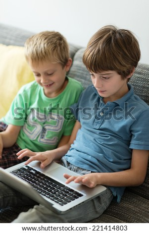 Two young brothers using a laptop computer surfing the internet together as they sit side by side on a sofa at home - stock photo